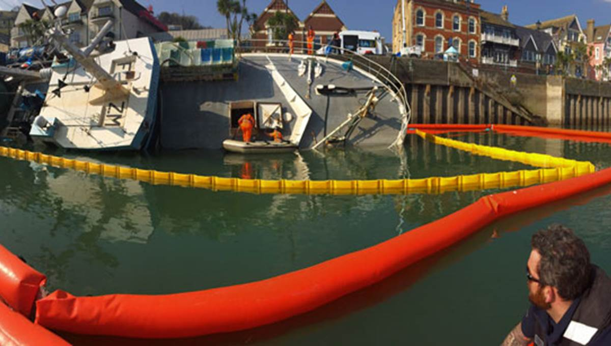 An overturned boat being worked on by a marine response crew